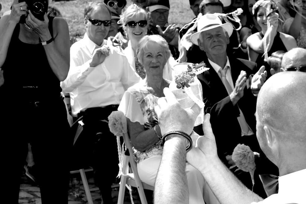 Hchzeitsfotografin fotografiert Bräutigam und die sitzenden Familienangehörigen