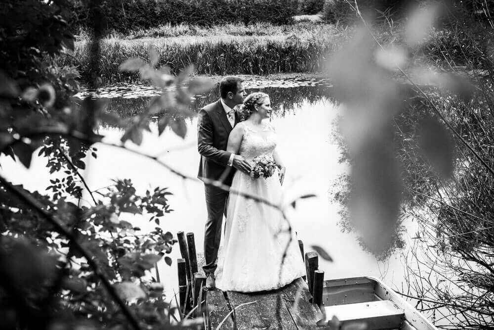 Hochzeitsfotograf aus Hannover stellt das Brautpaar auf einen Steg am See bild in SW
