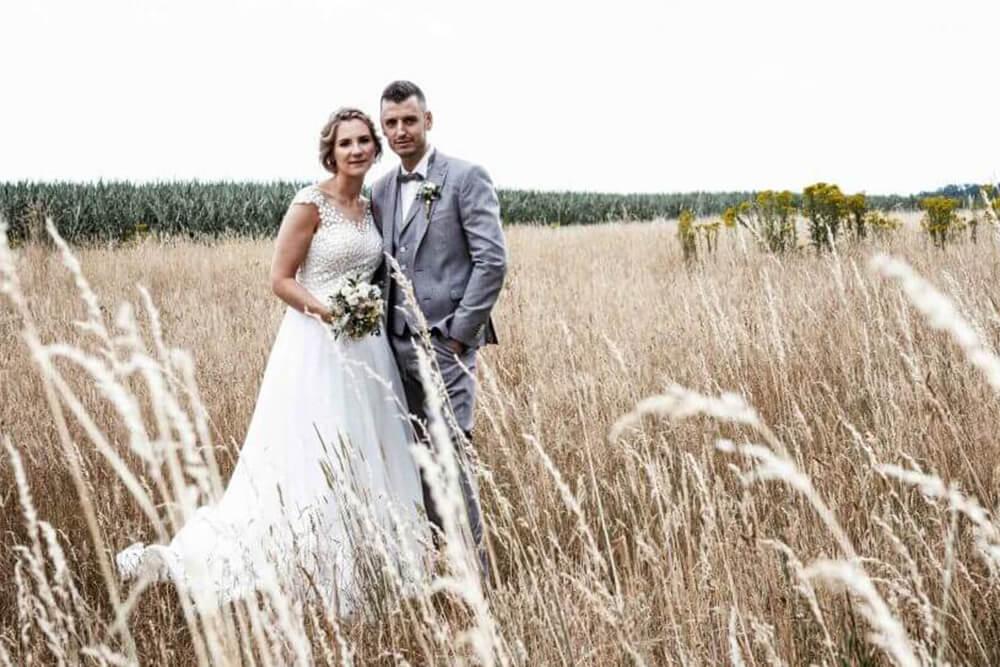 Hochzeitsfotograf positioniert stehendes Brautpaar auf einer Wies