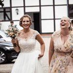 hochzeitsfotograf in Hannover hält Braut und Brautjungfer beim lachenden Spazieren gehen fest