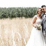 Ein Brautpaar im Kornfeld stehend sieht sehr glücklich und harmonisch aus in Zusammenarbeit mit dem Hochzeitfotograf aus Hannover