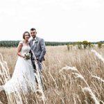 hochzeitsfotograf stellt Brautpaar in Kornfeld und lässt es entspannt aussehen.