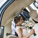 Sehr emotionelle Hochzeitsfotografie im Auto beim Einsteigen festgehalten von Hochzeitsfotografen